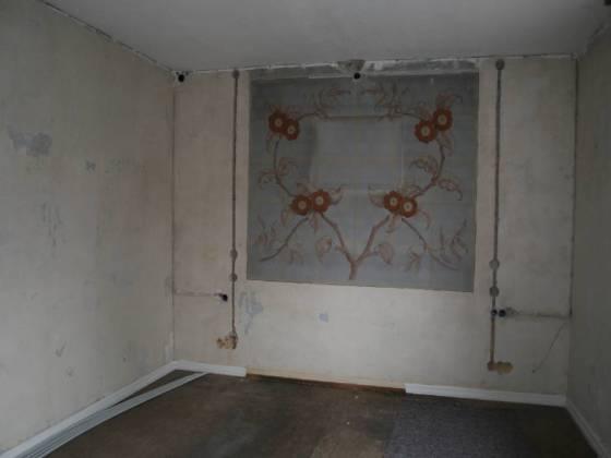 Das Schlafzimmer - Die Wandbemalung kan leider nicht erhalten werden. Zunächst werden die Schlitze für die Leitungen gesägt, die alle nach oben in die Decke führen.